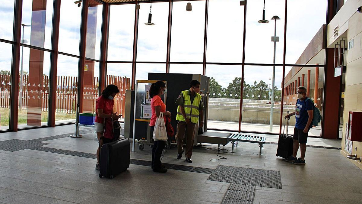 Varios viajeros conversan con el vigilante de seguridad en el interior de la estación. | A. S.