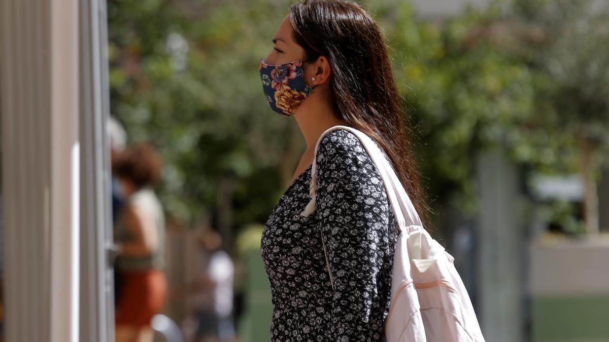 Una mujer pasea por una céntrica calle de València con mascarilla.