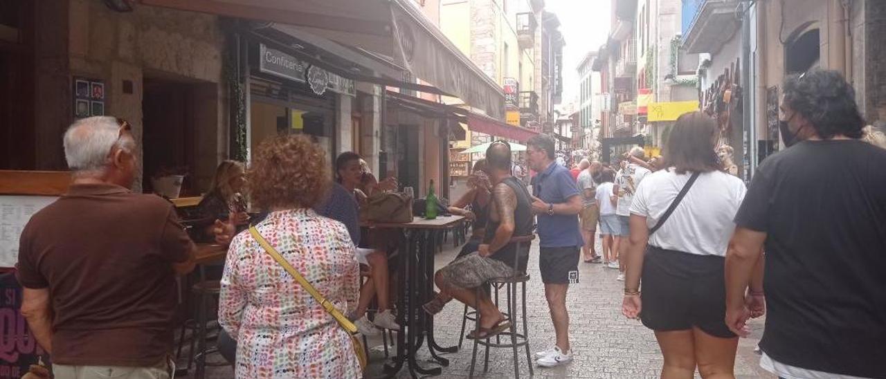 Personas paseando y consumiendo en la calle mayor llanisca.