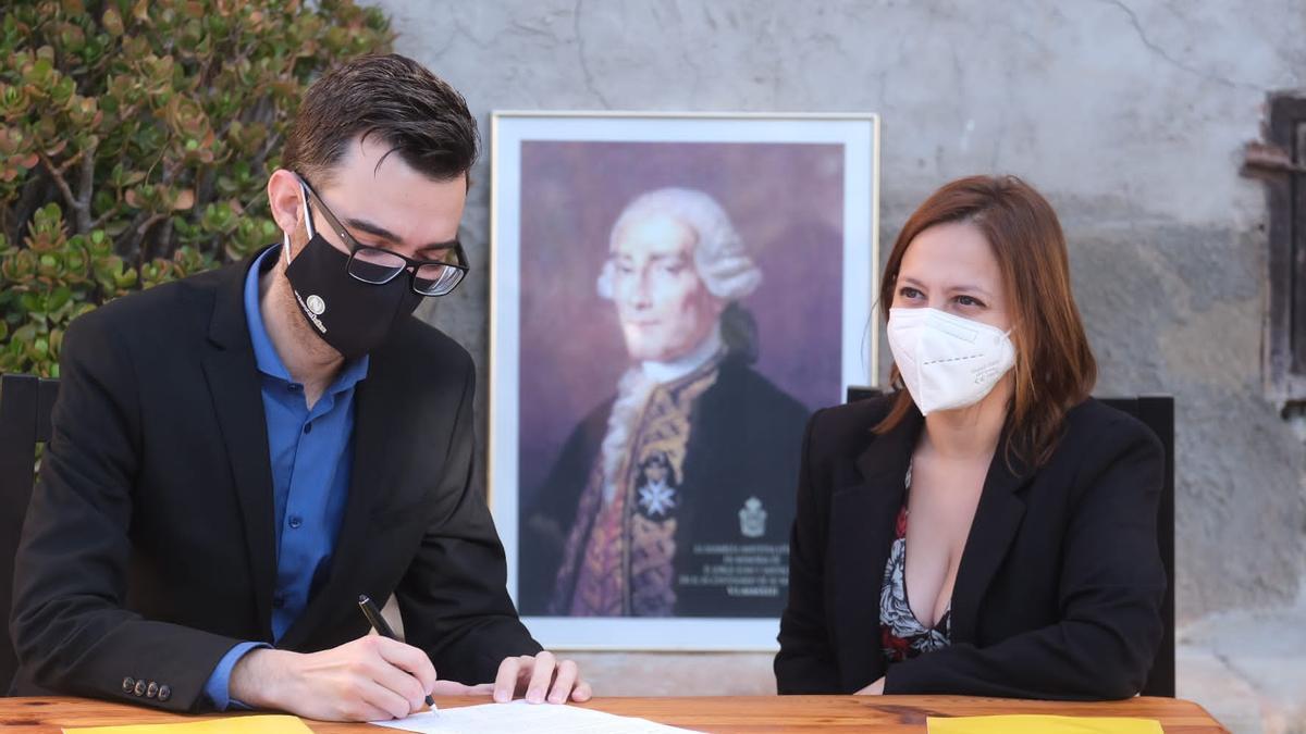 Los alcaldes Fran Martínez y María Dolores Berenguer firmando el acuerdo ante la foto del científico Jorge Juan.