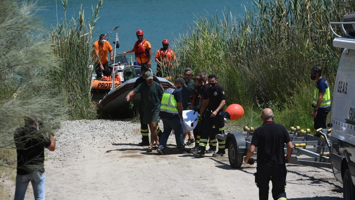 Policías, bomberos y guardias civiles trasladan el cadáver del joven ahogado en el Lago Azul de Córdoba, a quien se buscaba desde el domingo por la tarde.