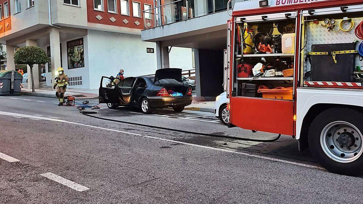 La intervención de los bomberos, revisando el vehículo tras sofocar las llamas.