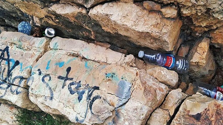 La basura y las pintadas llegan a la costa más recóndita de Xàbia