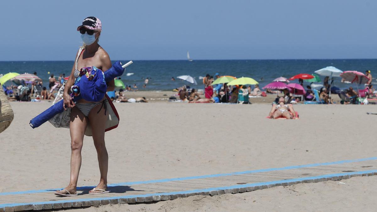 Una mujer, en la pasarela de acceso a la playa, con la mascarilla puesta.