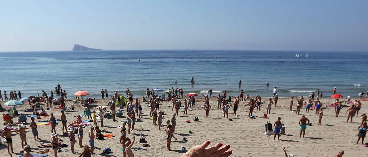 Turistas jubilados haciendo gimnasia en la playa de Levante de Benidorm hace dos años.   DAVID REVENGA