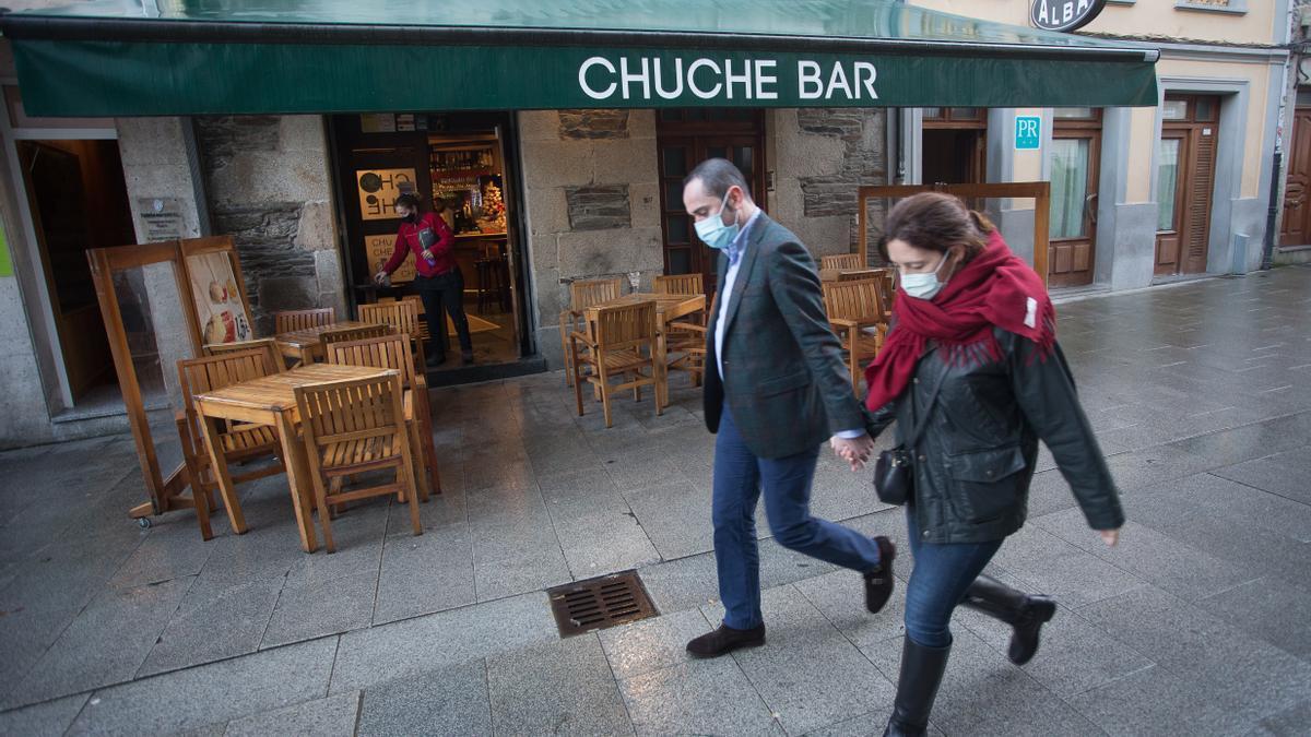 Dos persons pasan ante un bar en Lugo