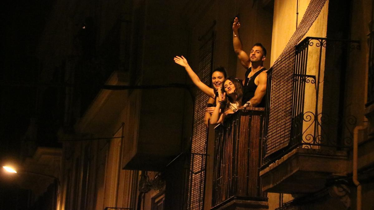 La silueta de diversos joves al carrer celebren el final del toc de queda a Gràcia