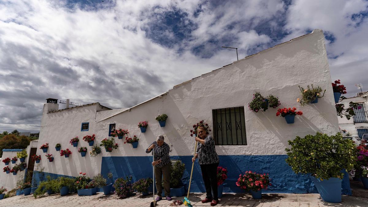 Dos vecinas barren la puerta de una de las fachadas engalanadas en Cañete.