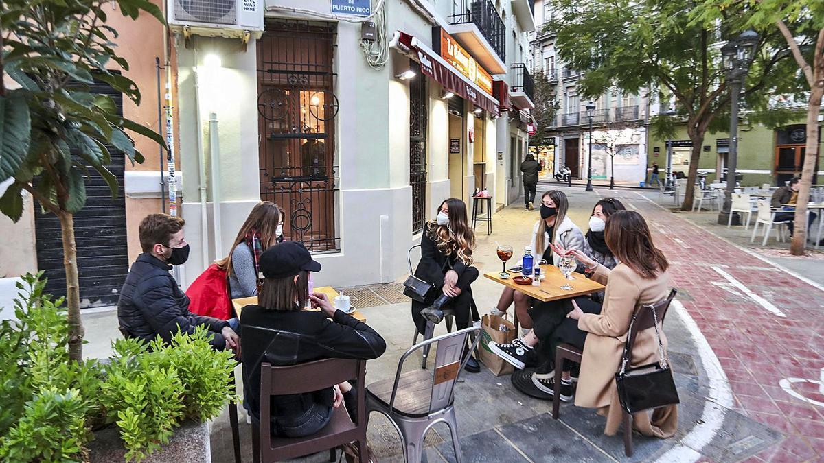 Clientas de una terraza de  València con la mascarilla  puesta, en una imagen  de ayer tarde. levante-emv