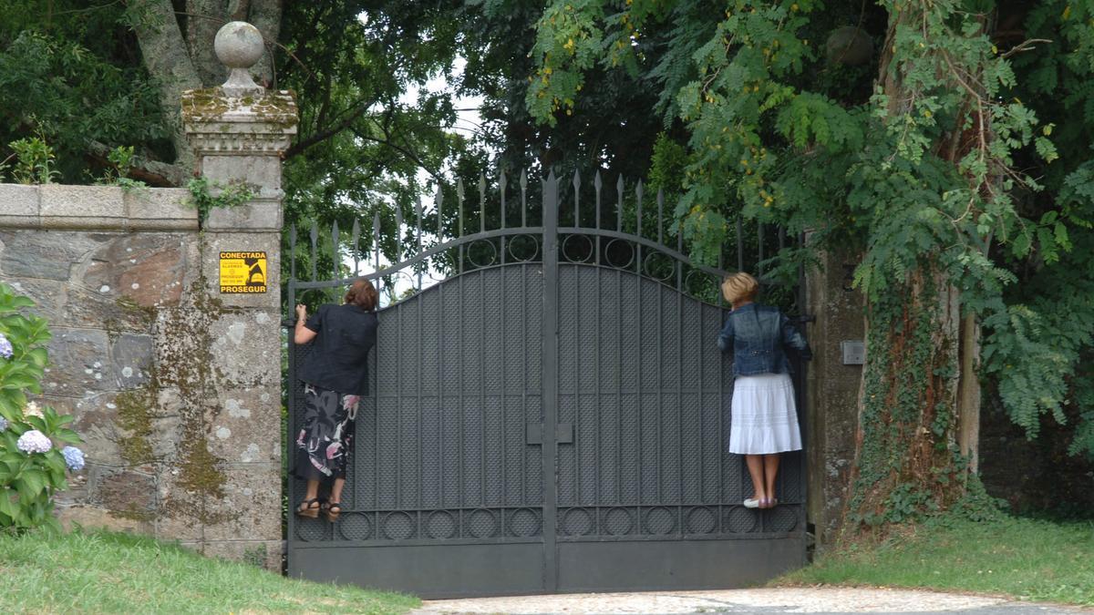 Dos mujeres encaramadas al portalón de entrada del pazo de Meirás para ver los jardines.