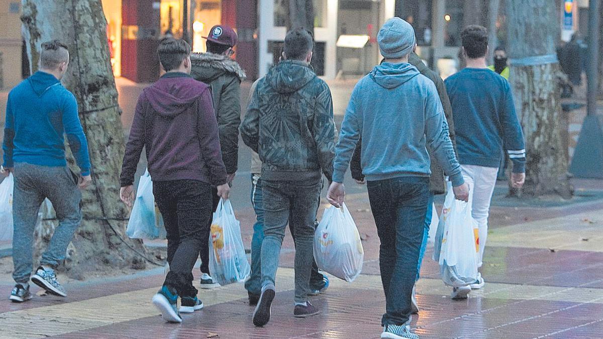 Un grupo de jóvenes, camino de un botellón con bolsas de bebida en una imagen de archivo.