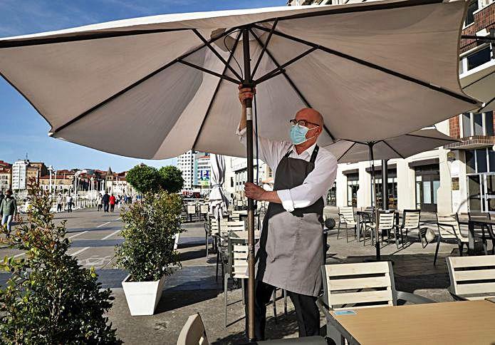 El hostelero Ignacio Robles colocando una sombrilla.