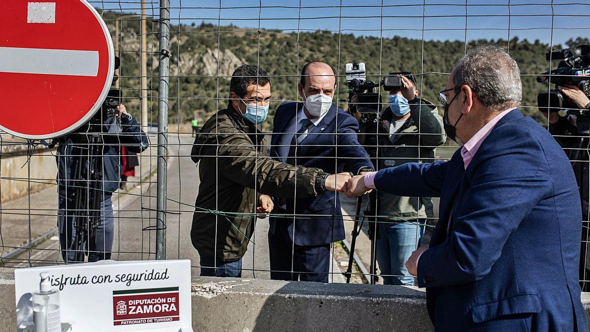 El alcalde de Fermoselle, de espaldas, saluda a los alcaldes de Bemposta y Miranda do Douro tras la alambrada en el paso de Bemposta. | Nico Rodríguez