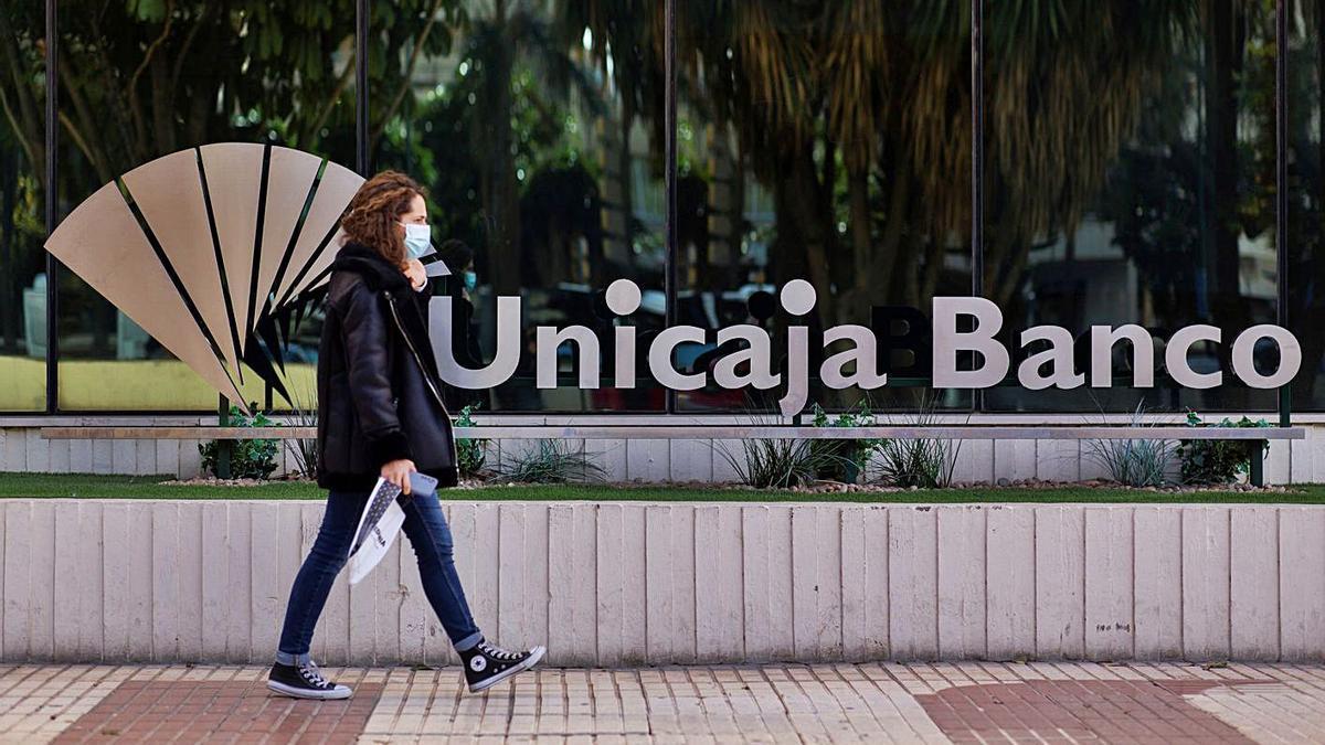 Una mujer pasea ante un letrero de Unicaja.