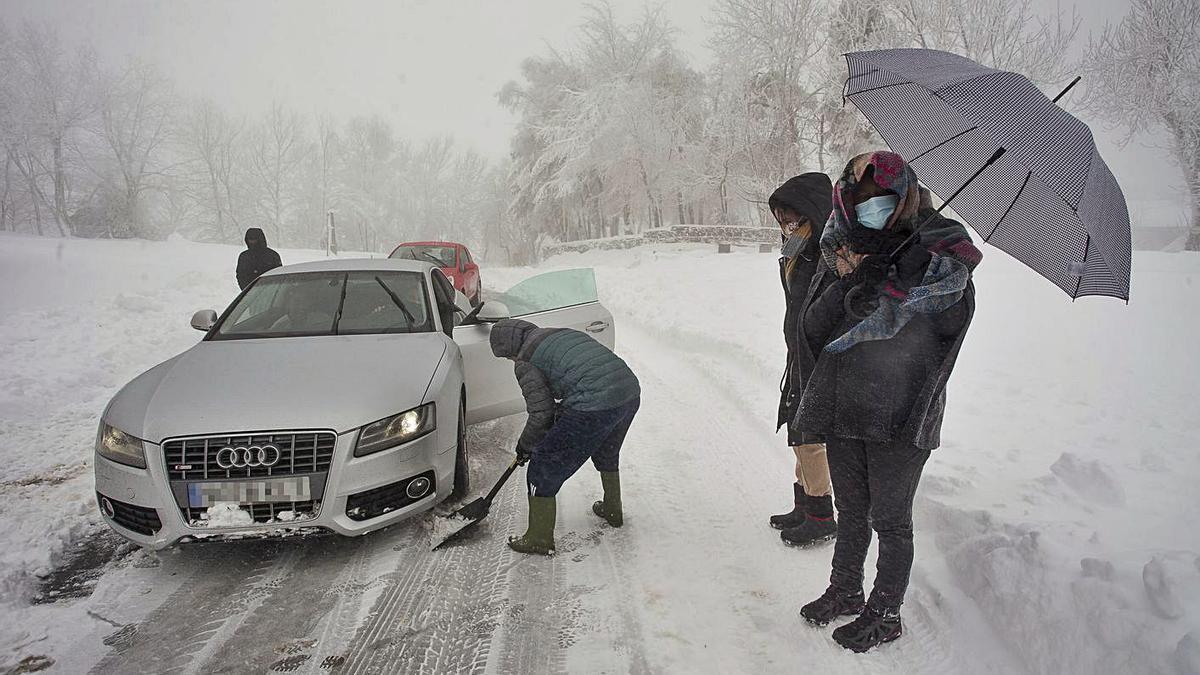 Varias personas limpian la carretera con una pala para ayudar a un coche atrapado en Pedrafita.  | // E. P.