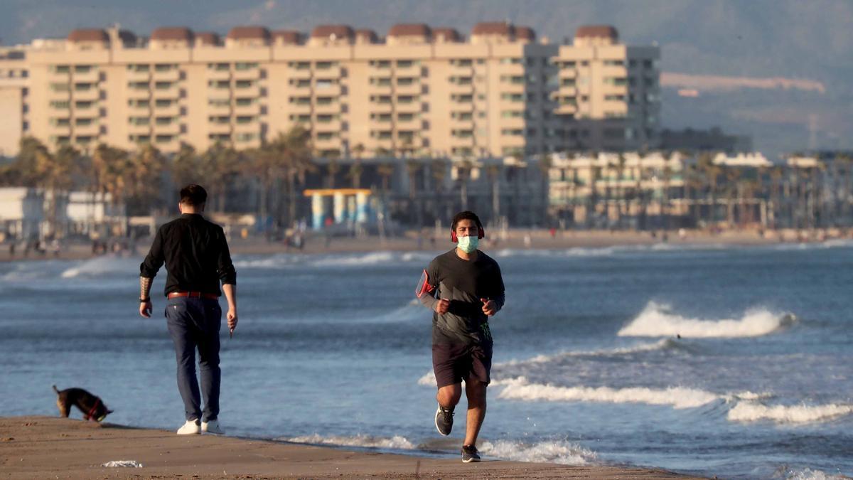 Un joven corre con mascarilla en la playa de la Malva-rosa de València.