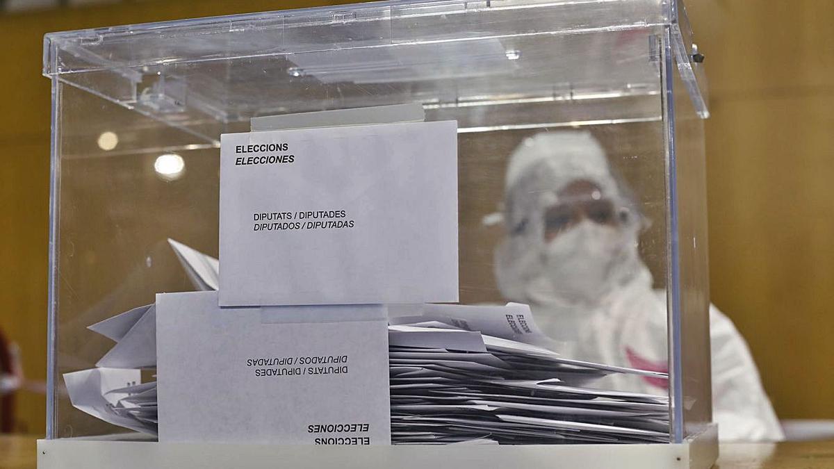 Un miembro de una mesa electoral aguarda la llegada de votantes, ataviado con un equipo de protección, durante las recientes elecciones catalanas.