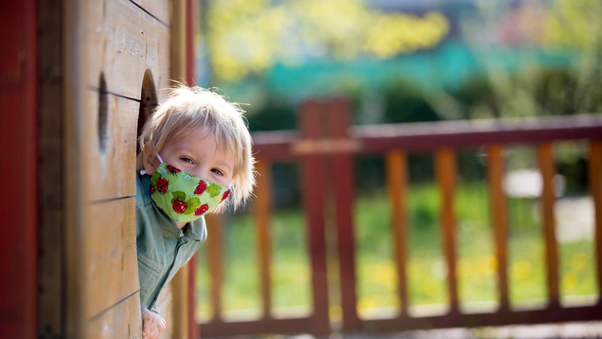 Una niña juega en el parque con su mascarilla.