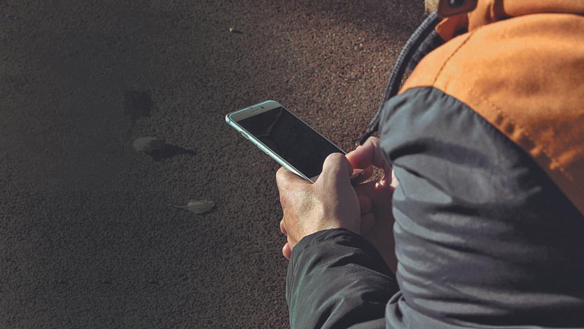 Un joven consulta su móvil. |   // LA OPINIÓN