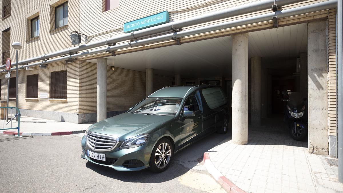 Un coche de una funeraria sale del recinto mortuorio del hospital Clínico.
