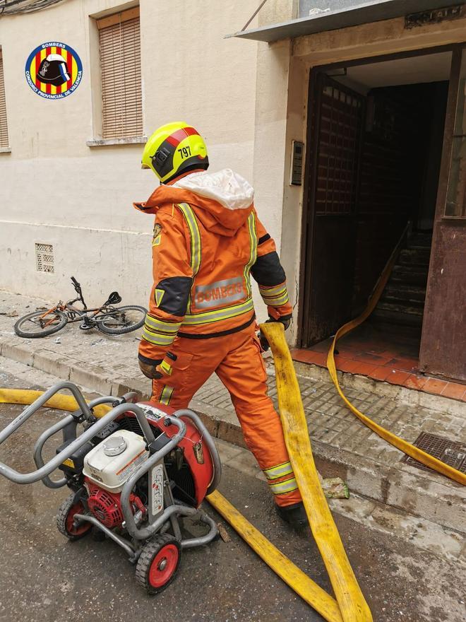 Un bombero durante el incendio en la vivienda de Algemesí que se ha cobrado una vida y tres heridos.
