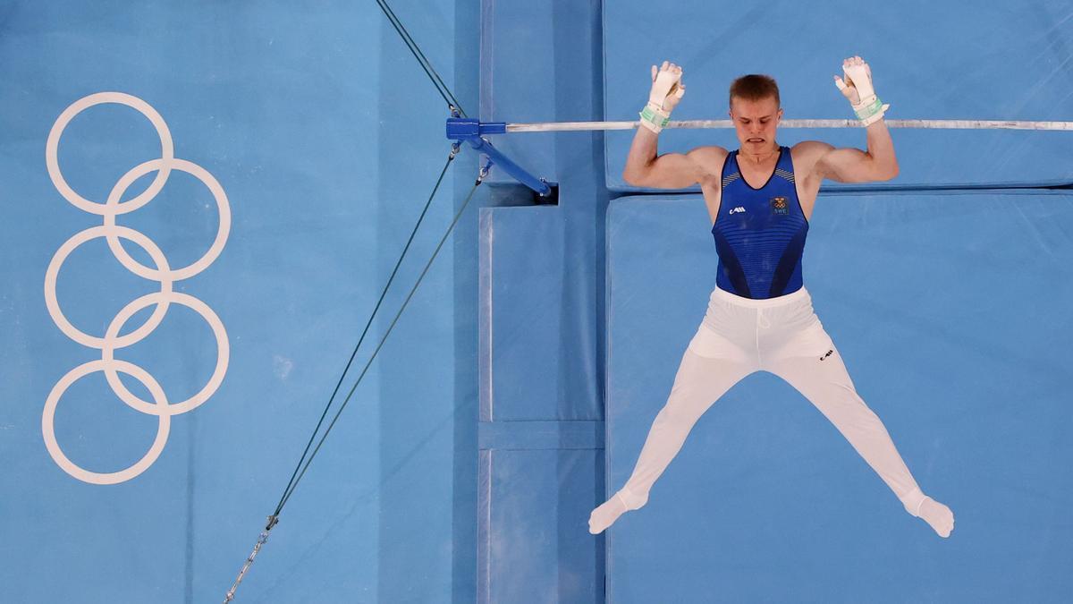 Un gimnasta entrena frente a los aros olímpicos.
