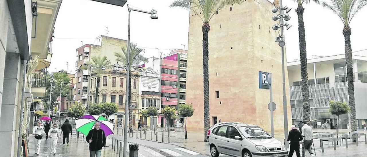 Coches sobre la zona peatonal de la Plaça Major, con la Torre y el Nou Mercat.