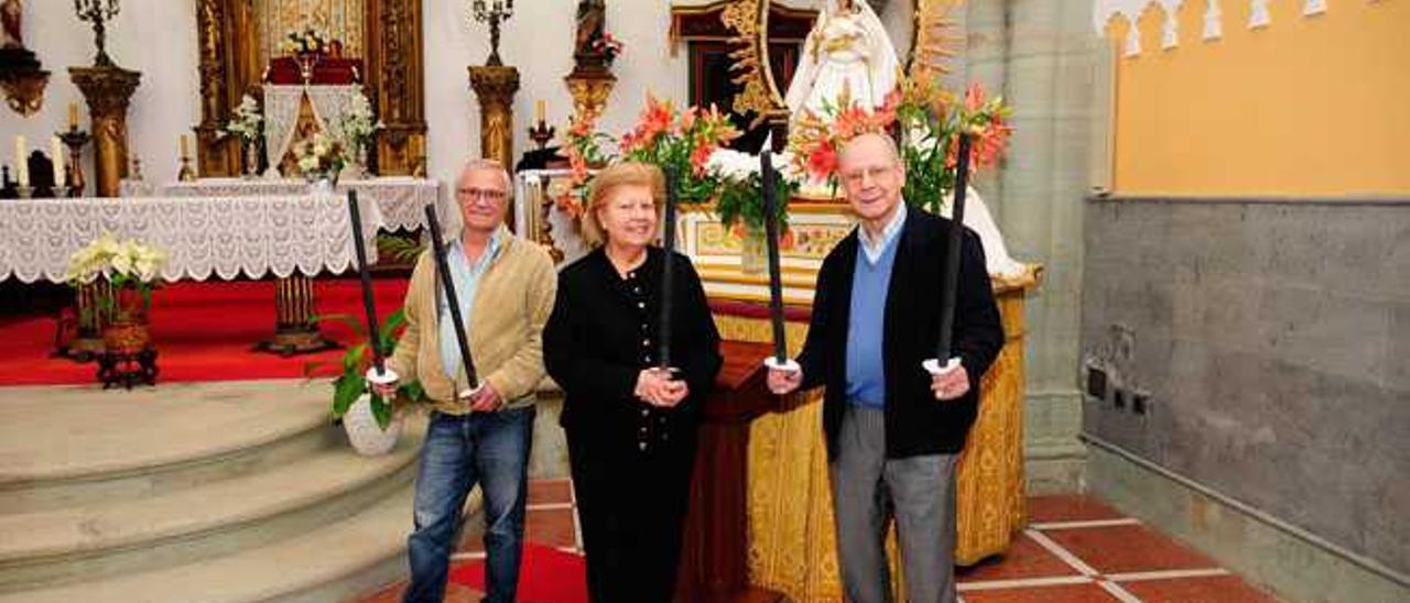 Rodrigo Rodríguez, María Reyes Ramírez y Eugenio Peñate, con varias de las antorchas, ayer, en la iglesia de Tara.