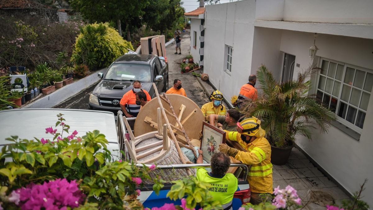 Bomberos y personal del Ayuntamiento ayudan a las familias a sacar enseres de sus casas antes de que llegue la lava del volcán.