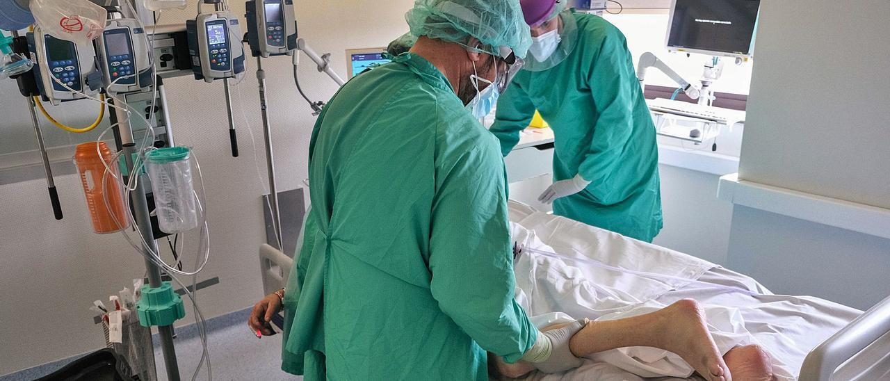 Sanitarios atendiendo a una paciente ingresada por covid-19 en la Unidad de Cuidados Intensivos.   ÁXEL ÁLVAREZ