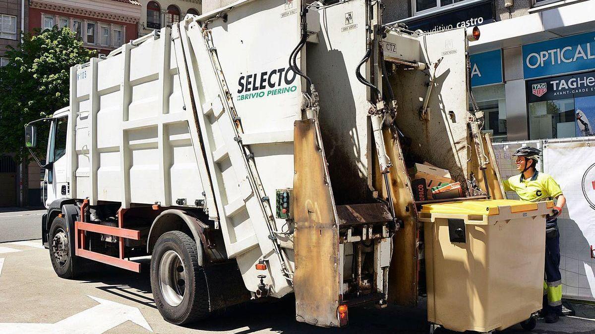 Un operario del servicio de recogida de basuras manipula un contenedor junto a un camión.