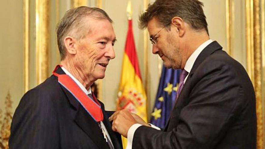 Ricardo Larraínzar recibe una condecoración del ministro de Justicia Rafael Catalá, en 2017. A la derecha, con la metopa que le dio el ministro Rosón.