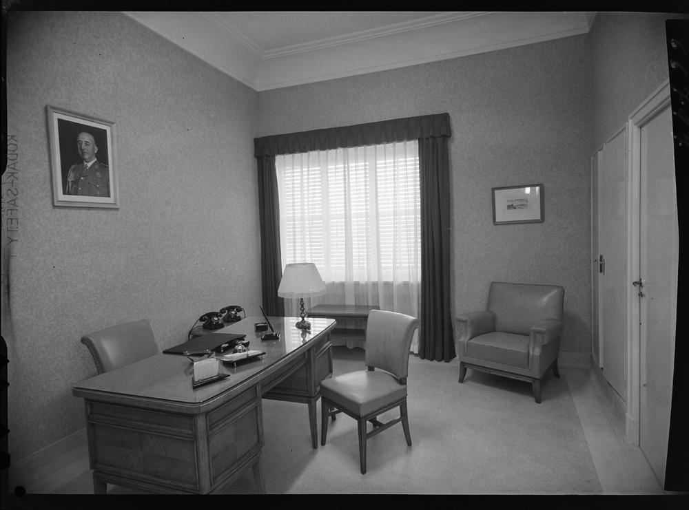 Interior de un despacho con mobiliario de madera y retrato de Franco en la pared.jpg