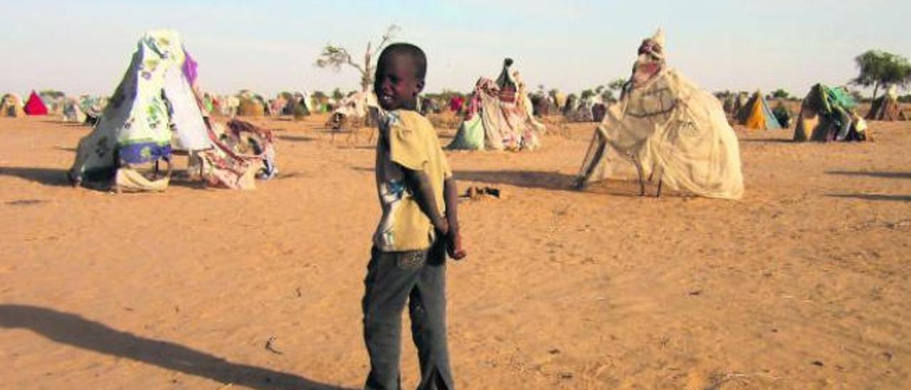 Un niño desplazado por el conflicto de Boko Haram frente a los abrigos que utilizan como casas en Diffa.