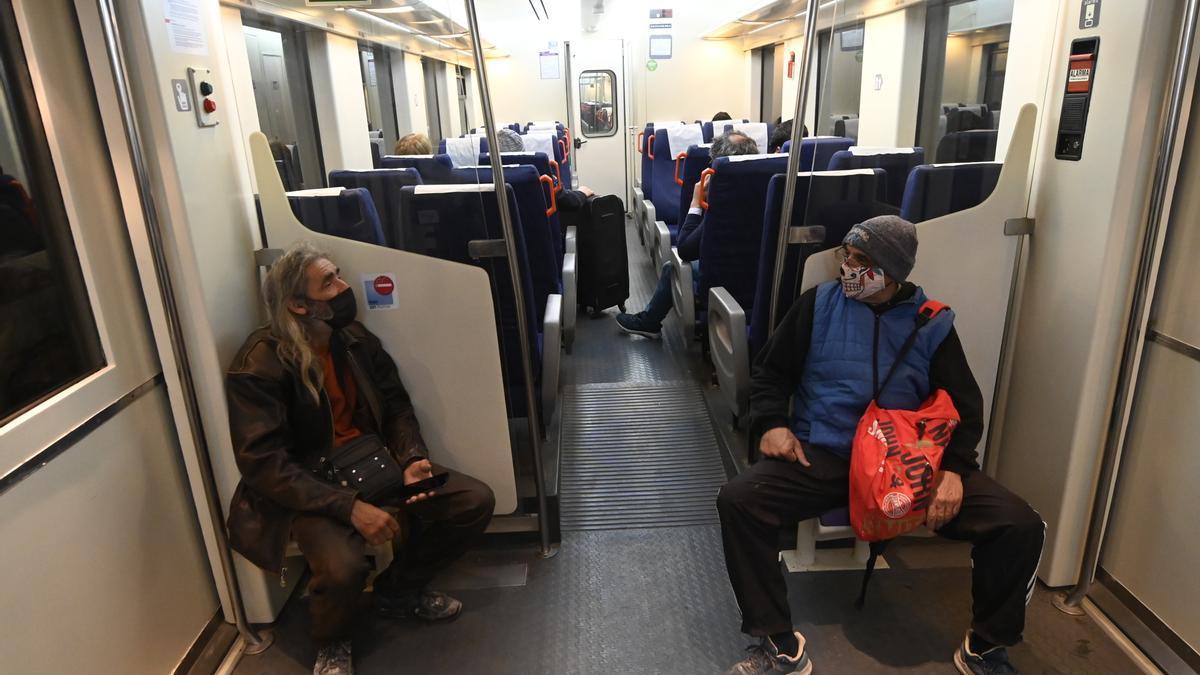 Varios pasajeros dialogan en un tren con dirección Vinaròs, a su salida desde la estación de la capital de la Plana.