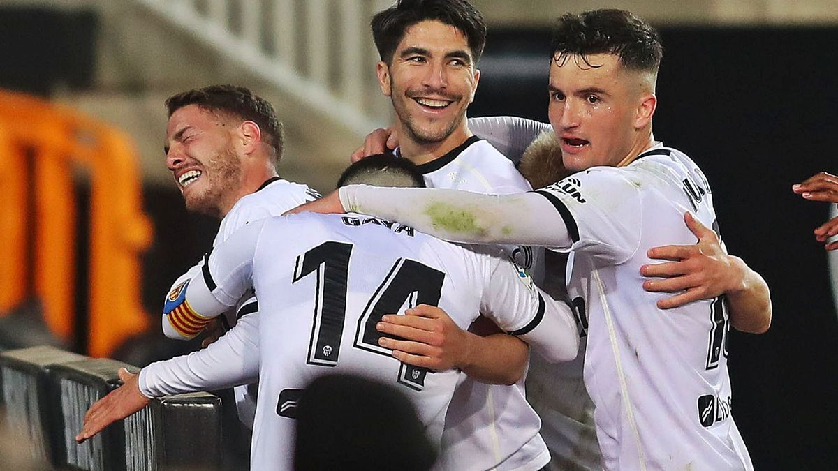 Manu Vallejo celebra el primer gol del Valencia CF, ya en el descuento, junto a varios compañeros.    F. CALABUIG/SD