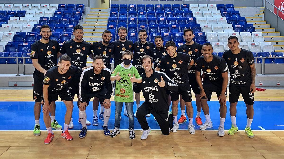 Iker Sánchez, estudiante de cuarto de Primaria del Colegio Sant Vicenç de Paül de Palma, posa con la plantilla del Palma Futsal. | PALMA FUTSAL