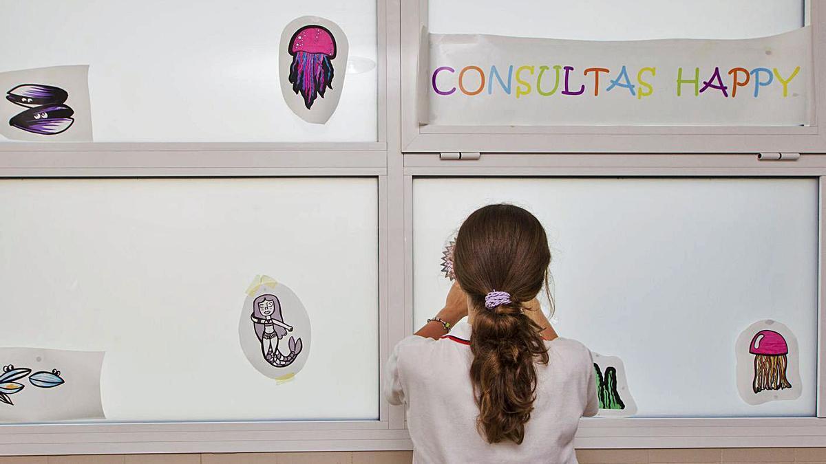 Una niña  ayuda a decorar el centro de salud en la Pobla de Vallbona. | GERMÁN CABALLERO