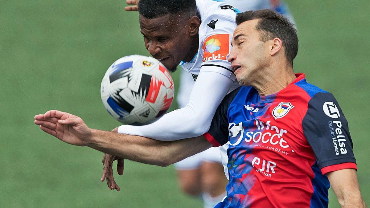 Uche Agbo pugna con el balón de cabeza durante el partido de ayer en Langreo. |  // LOF