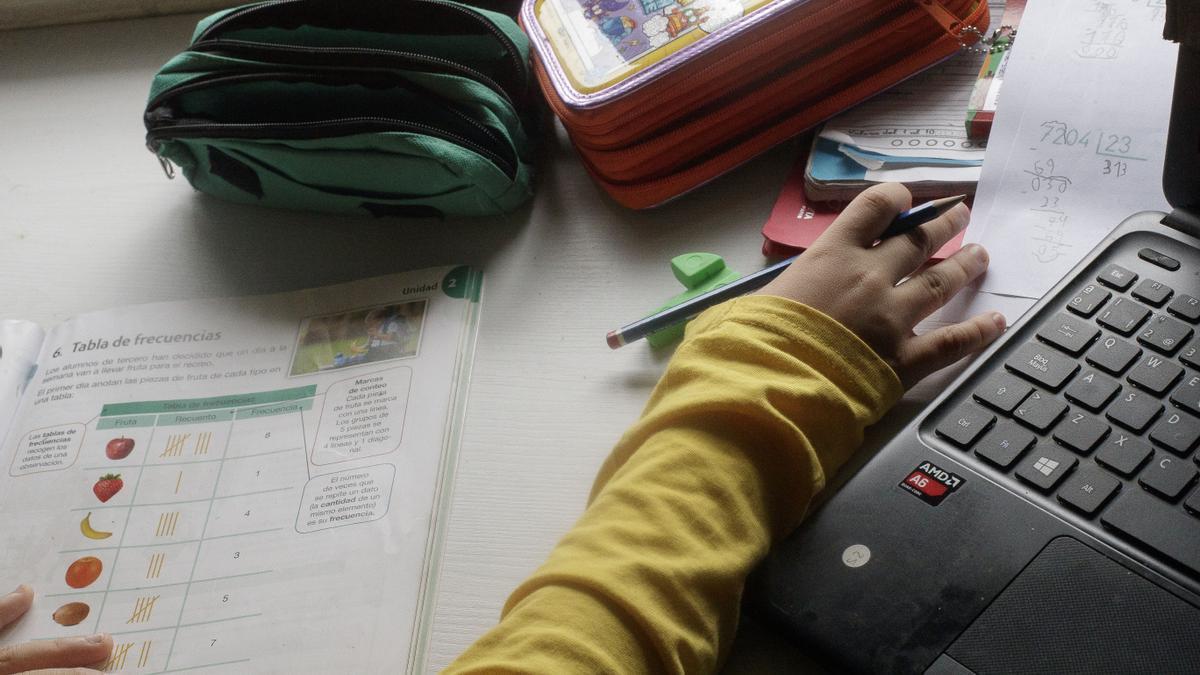 Un niño estudiando y haciendo los deberes.