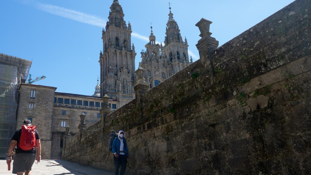 Un peregrinos con mascarillas se marcha de la Plaza del Obradoiro, mientras que otro llega, en el primer verano de la pandamia Covid-19, Santiago de Compostela 26 de agosto del 2020