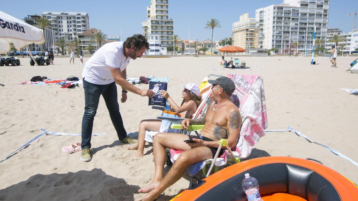 El concejal Mascarell entrega, ayer, un kit a dos bañistas de la playa de Gandia.
