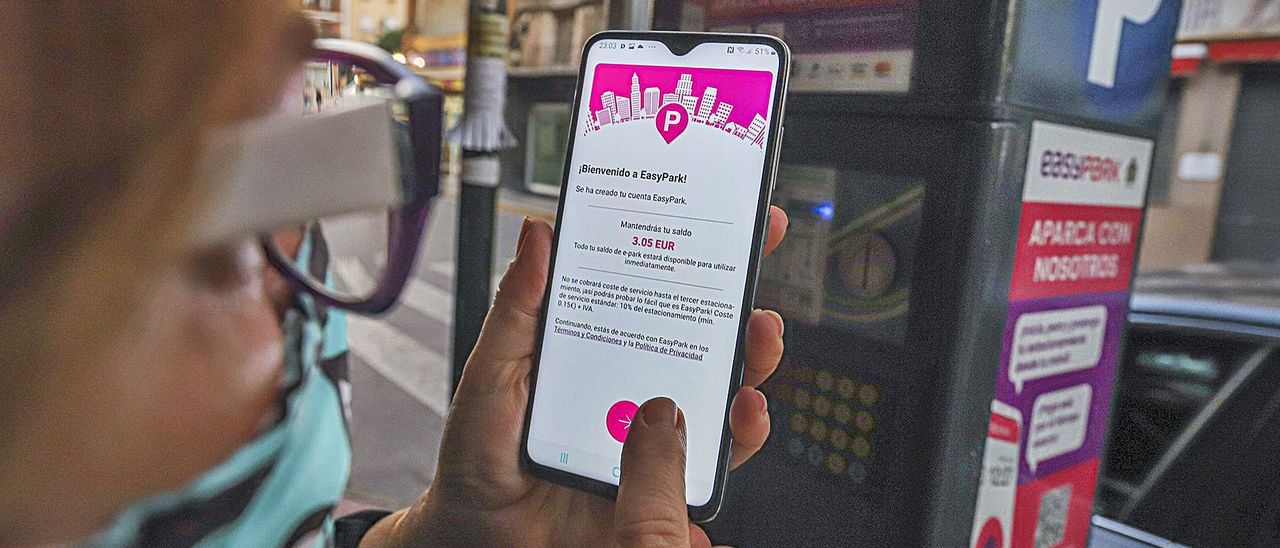 Una usuaria con la nueva aplicación que avisa del recargo, antes de pagar el ticket, ayer, por aparcar en la zona azul en la Plaza Nueva.