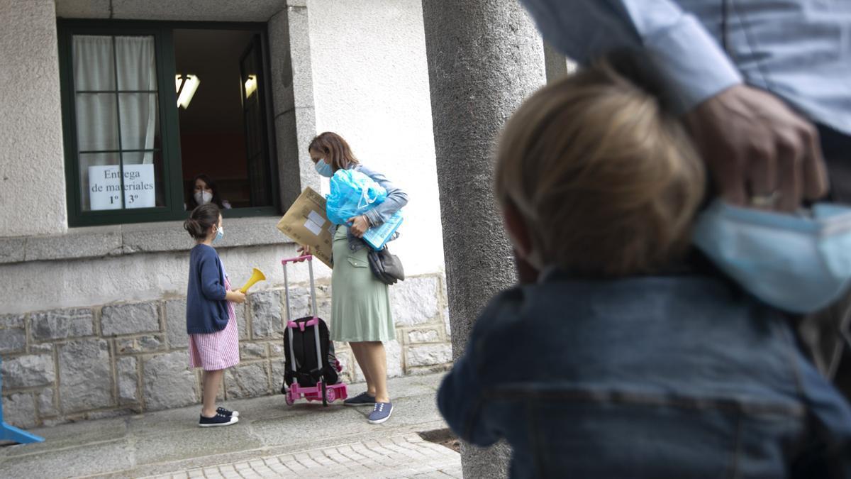 Niños recogen material escolar en un colegio junto a sus padres.