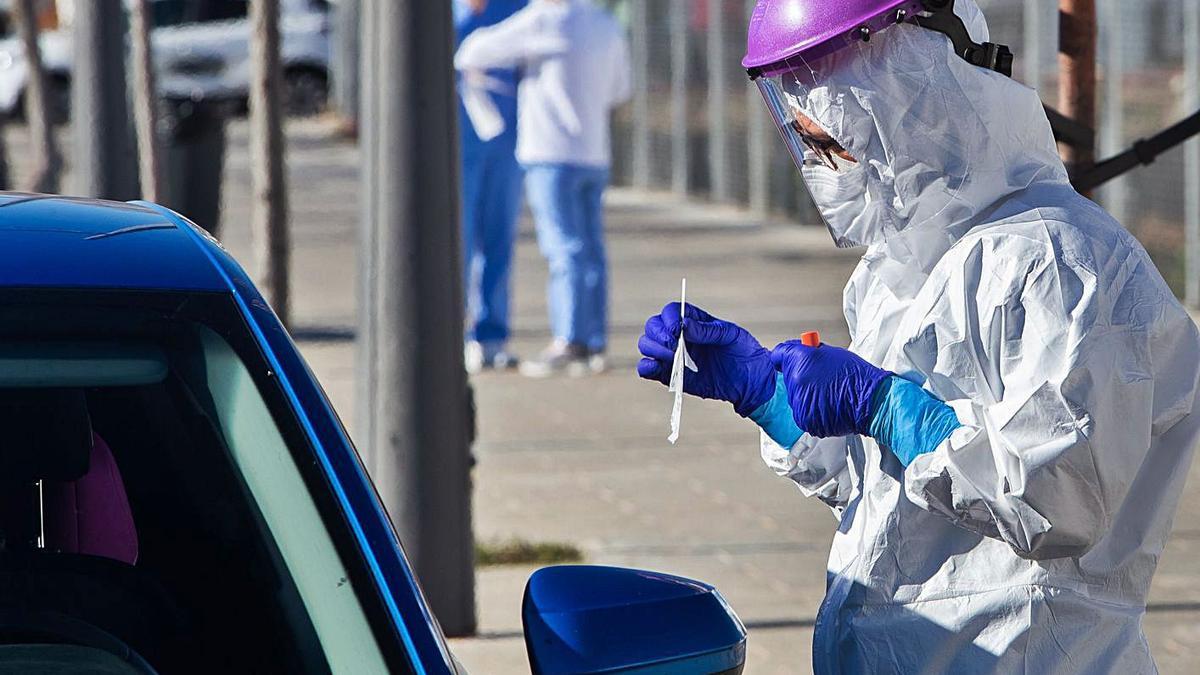 Una sanitaria realiza una  PCR a una persona en La Fe.  Germán caballero