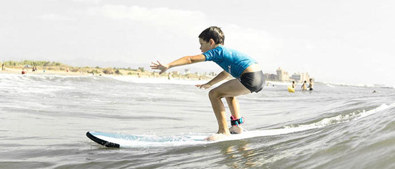 Un niño practica en una tabla de surf.