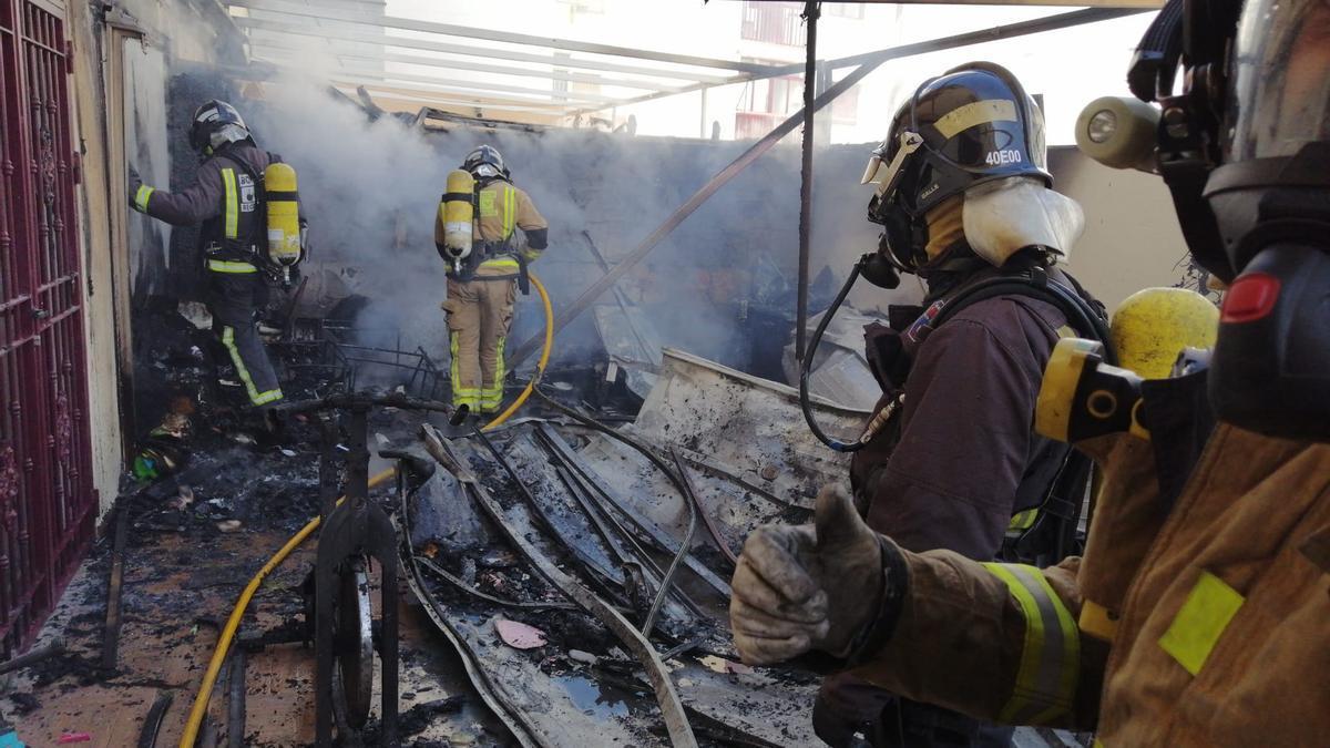Bomberos apagando los restos del incendio.