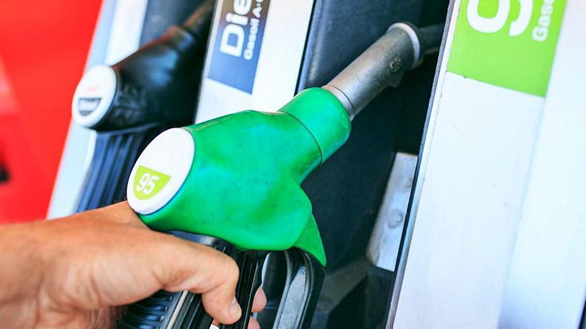 Un usuario de una gasolinera coge una de las mangueras dispensadoras de combustibles.