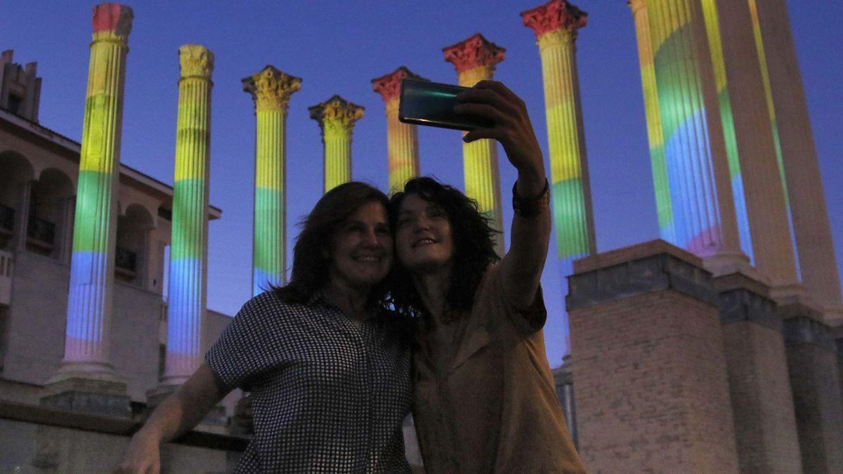 Dos chicas se fotografían delante de las columnas iluminadas con el arcoíris del Templo Romano.