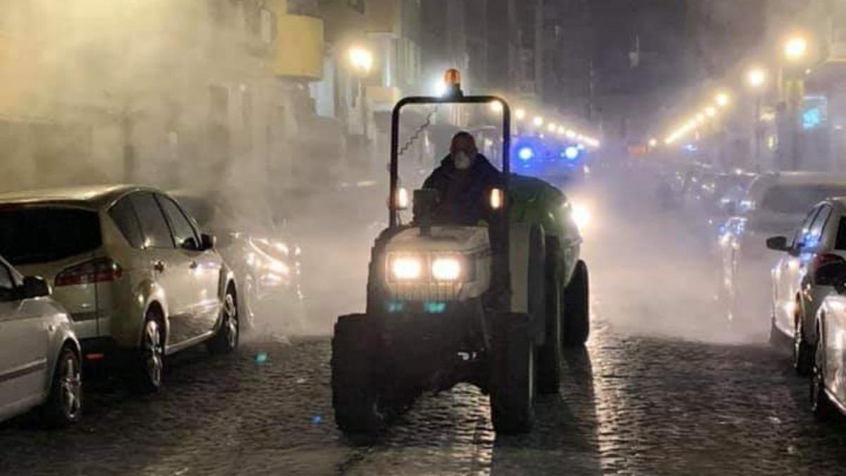 Uno de los tractores en plena fumigación desinfectante.